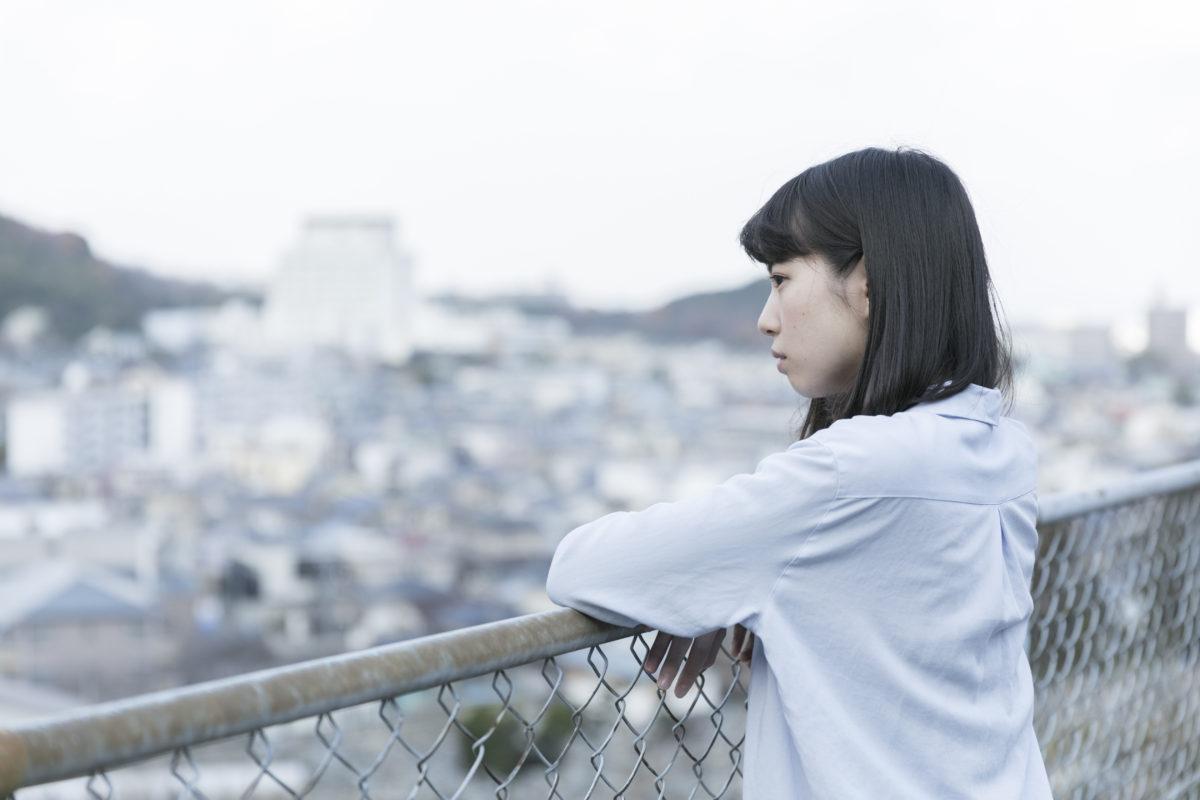 写真:コラム【経済的な不安6_小さなトラブルが生活崩壊に】高台から眺める女性