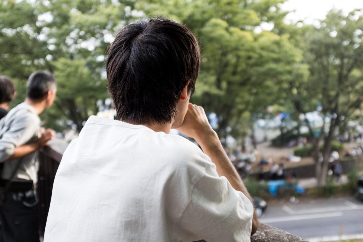 写真:コラム【経済的な不安2_高校卒業後の進路】歩道橋から眺める男性